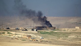Smoke rises from clashes as Iraqi security forces engage in a battle with Islamic State militants in