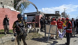 Pakistani security personnel gather with volunteers at the main entrance of a court complex