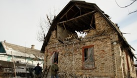 Men walk near a damaged house following shelling in Makeyevka