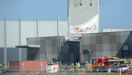 Fire crew at the scene where a light plane crashed into the back of a building at Essendon airport i