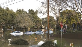 Flood waters flow around partially submerged vehicles at William Street Park, near Coyote Creek in S
