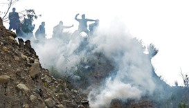 Bolivian coca growers from Los Yungas region confront riot police agents within a tear gas cloud, du