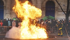 A firefighter tries to extinguish burning dustbins as students gather during a protest yesterday aga