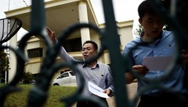 Embassy counsellor Kim Yu Song (L) gestures while reading a statement outside the North Korean embas