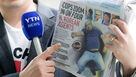 A reporter holds up a local newspaper during his report about Kim Jong Nam's murder