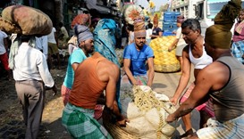 Indian labourers carry baskets of vegetables at the main wholesale vegetable market in Kolkata.