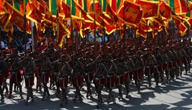 Members from the Sri Lankan military march with national flags during Sri Lanka's 69th Independence