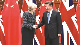 Chinese President Xi Jinping (right) shakes hand with British Prime Minister Theresa May on the side