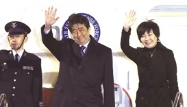Japan's Prime Minister Shinzo Abe and his wife Akie wave to people seeing them off from the governme