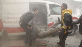 A Civil defence member carries an injured man amid dust after an airstrike in the besieged town of D