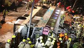 Firefighters and emergency personnel work at the site of an accident after a double-decker bus a top