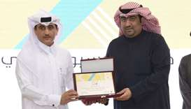 Kuwait's Minister of Commerce and Industry Khaled Nasser al-Roudan handing over the award to directo