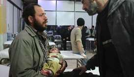 A Syrian man holds his infant who was rescued from under the rubble following air strikes on the reb