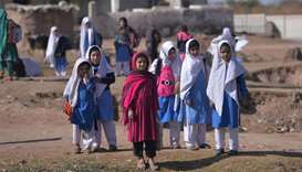 Afghan refugee girls leave after their school at a refugee camp on the outskirts of Islamabad