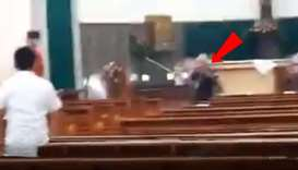 The attacker (pointed by the arrow mark) with a raised sword runs after a congregation member . Imag