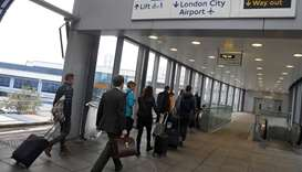 Passengers alight from a train to enter City Airport in London.