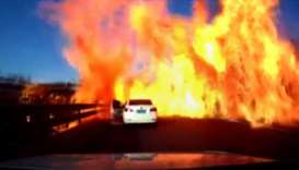 The door of a car (C) opening as a wall of flames ignites a long strip of motorway along the Beijing