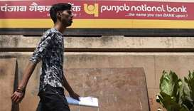 An Indian man walks past a sign for the state-owned Punjab National Bank (PNB) in Mumbai