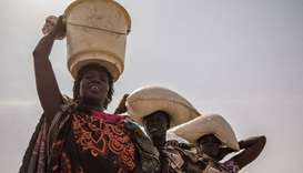 Women receive sorghum, beans, salt and oil for their families during a food distribution at the Prot