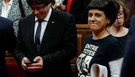 Leftist CUP party member Anna Gabriel (R) walks past Catalan President Carles Puigdemont