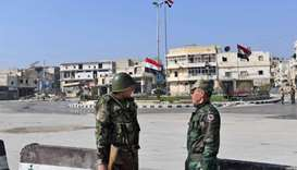 Syrian army soldiers are seen securing the entrance of Al-Haidieyeh neighbourhood in the northern ci