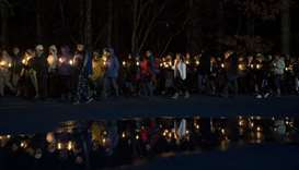 Mourners hold candles as they walk around the track of the football field during a community vigil a