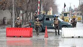 Afghan security personnel stand guard near the site of a suicide bombing in Kabul