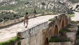 Turkish-backed Syrian opposition fighters walk on the Roman bridge in the archaeological site of Cyr