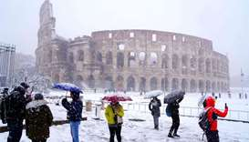 Tourists take pictures of the ancient Colosseum during a snowfall in Rome