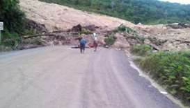 Locals inspecting a landslide and damage to a road located near the township of Tabubil after an ear