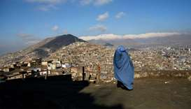 An Afghan woman walks on a hilltop overlooking Kabul