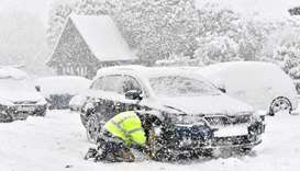 A man fits snow chains to his car in the village of Brenchley in southeast England