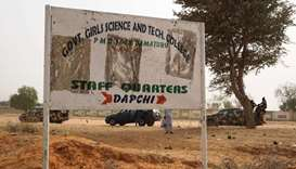 Soldiers (R) drive past a signpost leading to the Government Girls Science and Technical College sta
