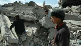 Syrian civilians search for survivors amid the rubble of buildings which were destroyed earlier in r