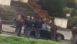 People gather where witnesses say a shooter was arrested in Macerata.