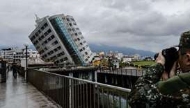 A rescue worker takes a photo of the Yun Tsui building, which is leaning at a precarious angle, in t