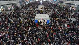 Crowds of travelers walk through a hall at a railway station in Hangzhou in China's eastern Zhejiang