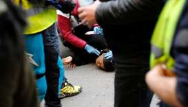Street medics provide first aid to a woman lying on the ground during an anti-government demonstrati