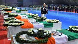 India's PM Modi pays tribute as he walks next to the coffins containing the remains of CRPF personne