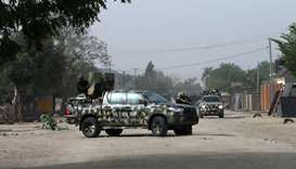 Nigerian military secure the area where a man was killed by suspected militants during an attack aro