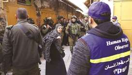 A Palestinian woman stands between Israeli soldiers and Palestinian Youth