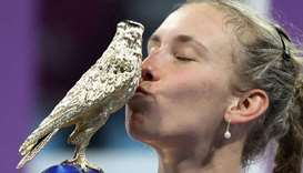 Belgium's Elise Mertens kisses the trophy as she celebrates after winning the final
