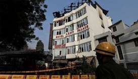 A fireman stands outside the hotel where a fire broke out in New Delhi