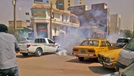 Tear gas smoke is seen amidst cars after Sudanese security forces used it to disperse protesters