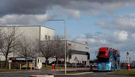A car transporter loaded with new Honda vehicles is driven out of the Honda manufacturing plant in S