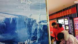 "People sitting next to a poster of Chinese sci-fi film ""The Wandering Earth"" in Yichang in China's c"