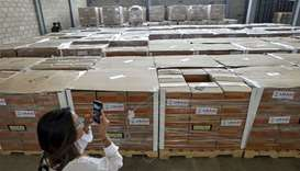 A woman photographs boxes containing humanitarian aid for Venezuela inside a warehouse at the Tiendi