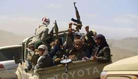 Armed Yemeni men raise their weapons as they gather near the capital Sanaa