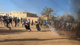 Sudanese demonstrators run from a teargas canister fired by riot policemen to disperse them as they