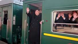 North Korean leader Kim Jong Un waves from a train as he departs for a summit in Hanoi, in Pyongyang